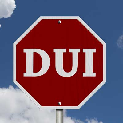 Stop sign with the word DUI written on it instead of the word stop.