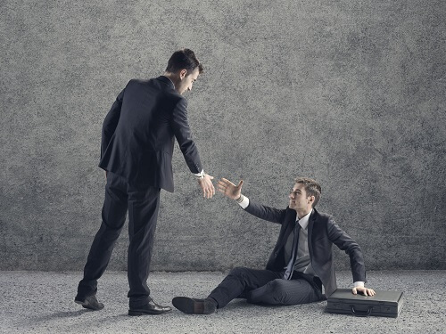 a business man helping another business man off the ground for blog post featured image